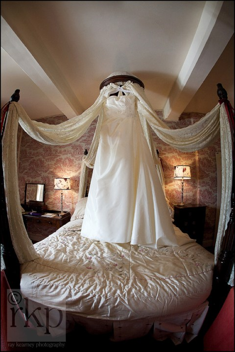 Bride's dress hanging uo on four poster bed at Soughton Hall