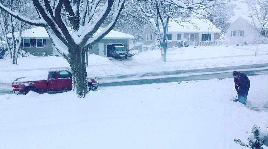 A neighborhood street, including trees, shrubs, and cars, is covered with snow. A man shovels snow off of his driveway.