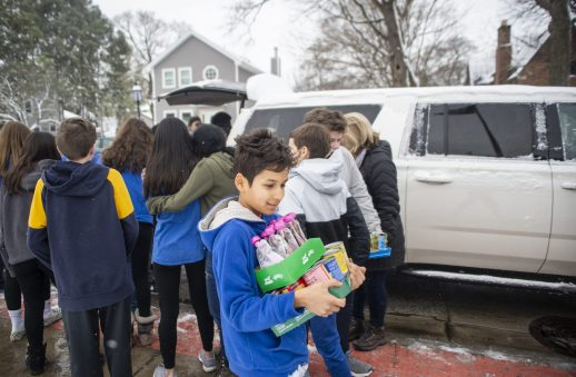 Seventh-grader Avi Ponnappan carries donations inside on Feb. 26, 2020, during the 50th annual food drive at L.J. Hauser Junior High School in Riverside. | ALEX ROGALS/Staff Photographer