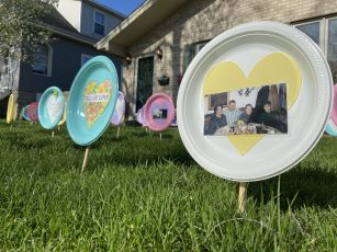 Photos and written memories, affixed to plastic plates and planted in the front lawn of the Polcyn home, are way for family and friends to grieve and pay respects for their their friend Carol Polcyn. | Photo by Bob Uphues/editor