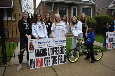 Fenwick's girls soccer team and Marlin Grant Jr. pose with his new bike that the Friars assembled last April (photo provided by Joe Trost).