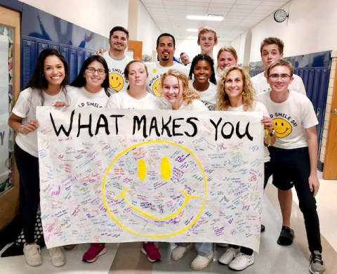 The RBHS Best Buddles Club celebrated World Smile Day with a banner and a video. Holding the banners are (front row, from left) Lily Favela, Ruby Pelayo, Marissa Bloodgood, Amanda DiForti, Anysiah Taylor, Dawn Soprych, Colin Griffin, (back row) co-sponsor Mitch Zilinger, Principal Hector Freytas, David Waas, Audrey Connelly and Jack Pitts. (PROVIDED)