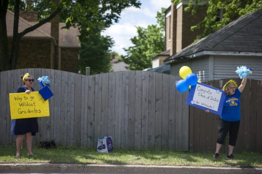 Pedestrians wave signs and cheer as graduates pass on Saturday, May 30, 2020, during Komarek School's graduation parade along 26th Street in North Riverside. | ALEX ROGALS/Staff Photographer
