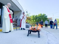 Father Denis Condon, left, blesses the bonfire while Deacon Dave Brencic, right, holds the Pascal candle during their Pentecost Vigil Celebration at St. Barbara Church in Brookfield.