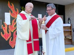 Father Denis Condon (left) and Deacon Dave Brencic light the Pascal candle during the Holy Guardian Angels Parish Pentecost vigil at St. Barbara Church in Brookfield on May 30.