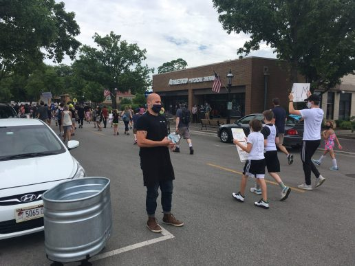 Riverside Foods co-owner Peter Boutsikakis hands out bottles of water to marchers sweating from the 90-degree heat as they headed east on East Burlington Street in Riverside during an anti-racism demonstration on June 9. | Bob Skolnik/Contributor