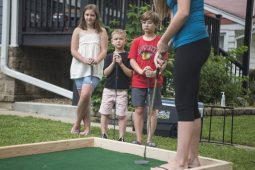 From left, siblings Jane Cwik, 11, Gunnar Cwik, 6, and Killian Cwik, 9, watch Ella Giampietro play on Sunday, June 28, 2020, during the Brook Park Council Summer Camp Progessive Putt Putt throughout Brookfield and Riverside. (Alex Rogals/Staff Photographer)