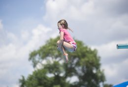 Children enjoy cooling off in the heat by jumping off the diving boards on July 26, at the Riverside Swim Club in Riverside. (Alex Rogals/Staff Photographer)