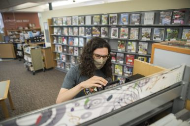 Dan Camponovo, of Brookfield, flips through DVDs at Brookfield Public Library. on Aug. 17, the first day the library reopened its doors to patrons for drop-in visits to browse the collection. (Alex Rogals/Staff Photographer)