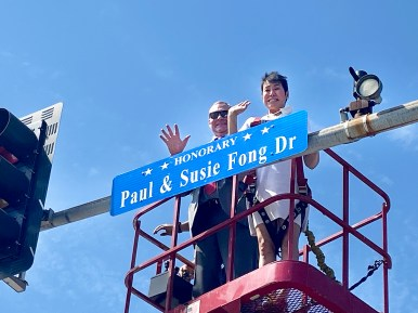 Dr. Lisa Abrams (right), the daughter of Chef Shangri-La founders Paul and Susie Fong, and North Riverside Mayor Hubert Hermanek Jr. wave to family and friends gathered for the unveiling of honorary streets signs at 26th Street and Desplaines Avenue on Aug. 13. (Bob Uphues/Editor)