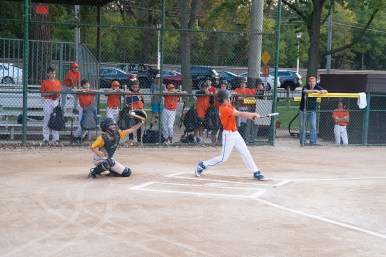 A batter for Western Springs (in orange) swings and misses on a pitch during the championship game of the 57th Annual Roy Overholt Tournament on Oct. 9 in Brookfield, but the setback was temporary as they defeated LaGrange Park 5-1. (Shanel Romain/Contributor)