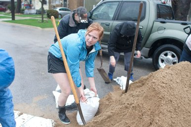 Krystal Krejcik and some of her neighbors fill sand bags with water from the Salt Creek rising to cover parts of Forest Avenue in Brookfield Thursday.