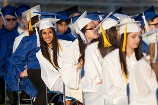 A graduating senior smiles as she spots a familiar face in the stands. (David Pierini/staff photographer)