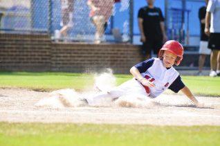 Youth league baseball player sliding home.