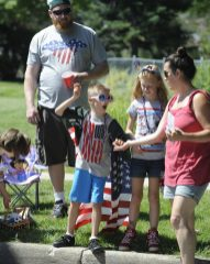 Francis Marino; 7 of Brookfield, and his friend Lily Trekles; 8 of Brookfield, grab some candy along the route; Ben Trekles looks on.