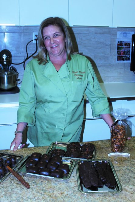 Donna standing among her variety of bacon confections