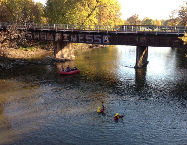 Personnel both in the water and in an inflatable boat check the river near Canadian National railroad bridge.Photos by Bob Uphues/Staff
