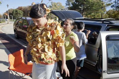Jocelyn Rodriguez wanted to look like an overflowing bag of leaves and had her mother, Tammy, stick leaves to her with duct tape. In the background, Jocelyn's brother, Jonathan, applies some face paint with the help of window reflection.