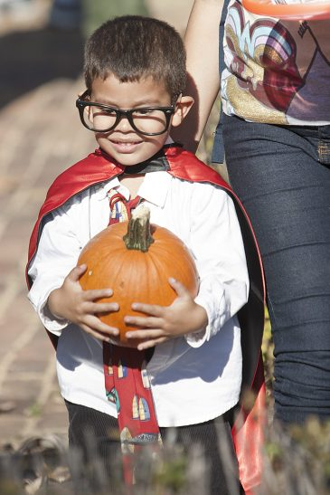 Julian Banda, 3, is happy with the pumpkin he received as part of the event. He was Clark Kent in mid-transformation to Superman.