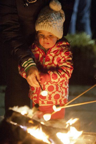Josephine McAllister, 2, carefully roasts a marshmallow during the Riverside Holiday Stroll Friday. (David Pierini/staff photographer)