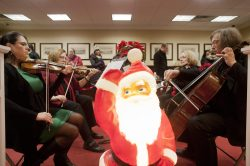 Members of the West Suburban Symphony plays holiday music in the lobby of the Riverside Bank while families stand in line to see Santa at the annual holiday stroll. (David Pierini/staff photographer)