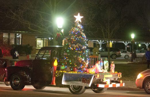 A motorist rides through the center of town in a vintage pickup truck festooned with Christmas decorations during the Riverside Holiday Stroll Friday. (David Pierini/staff photographer)