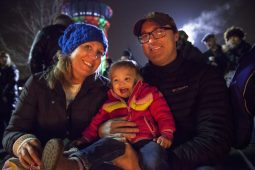 """Over near Riverside Garage just across the way, the Jackson family warms up near a fire with their 1-year-old daughter. They came to the Stroll because """"this is her first Christmas where she knows who Santa is."""""""