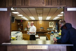Finance Director Doug Cooper assists a citizen from inside their makeshift office inside the Edward J. Barcal court room of the Brookfield Village Hall on Friday, January 9, 2015. The court room is acting as a makeshift office as the rest of the village hall is renovated. | Chandler West/Staff Photographer