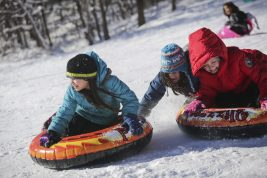 (From left) Sisters Stella and Clara Pizana, both 10, with friend McKenna Sunderland, 9, pick up speed on the sled hill at Swan Pond park on Monday, February 3, 2015. | CHANDLER WEST/Staff Photographer