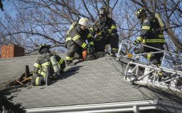 Firefighters cut holes in the roof of the residence at 9129 Washington Ave. in order to vent the attic.