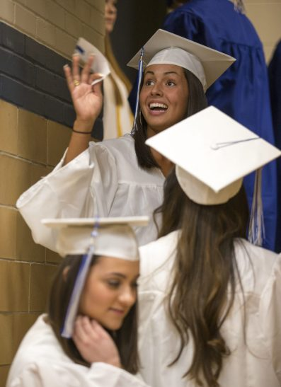 A graduating senior waves at family and friends before stepping on stage to receive her diploma during the commencement ceremony at Riverside-Brookfield High School.   Ting Shen/Contributor