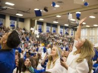 Graduating seniors of class 2015 toss their caps in the air and embrace family members at the finish of the commencement ceremony at Riverside-Brookfield High School on May 22. | Ting Shen/Contributor