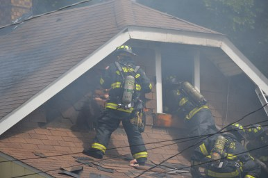 Firefighters get a look inside the bungalow at 3308 Sunnyside Avenue in Brookfield via an upper-story window. The back end of the home was heavily damaged by flames. (Photo by Code Photography)