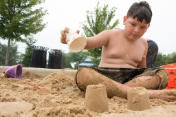 Noah Martinez shovels and compounds sand to build the mound for a sand castle Saturday, July 11 at the Ehlert Park volleyball court.