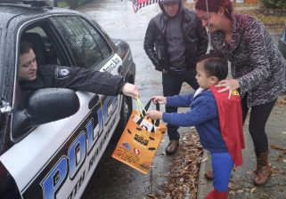 Julian Tapia gets a glow stick and candy from a North Riverside police officer while trick-or-treating in North Riverside despite persistent rain on Halloween on Saturday, Oct. 31.   William Camargo/Staff Photographer