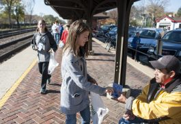 Mia Scharpf hands a note to a commuter at the downtown train station. | William Camargo/Staff Photographer