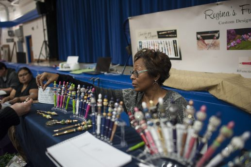 Regina Ferguson, whose booth at the North Riverside Holiday Arts and Crafts Fair at the Village Commons on Nov. 7 included an artistic array of unique pens, assists a customer with a purchase. | William Camargo/Staff Photographer