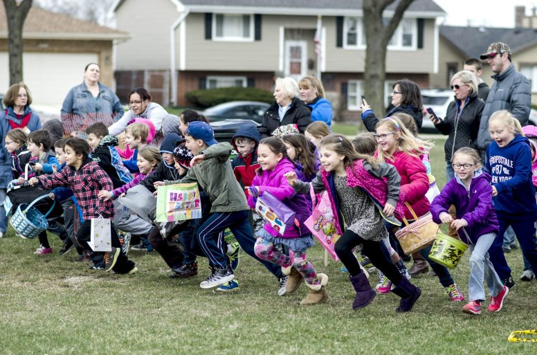 Kids sprint toward a field of plastic eggs to claim their share during the Brookfield Chamber of Commerce's annual Easter Egg Hunt at Ehlert Park on March 19. | William Camargo/Staff Photographer