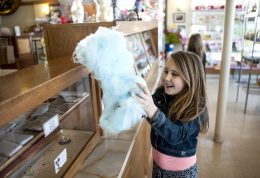 Cali Melidis enjoys a hunk of cotton candy before browsing for Easter candy at Aunt Diana's Old Fashioned Fudge in downtown Riverside on March 25.   William Camargo/Staff Photographer