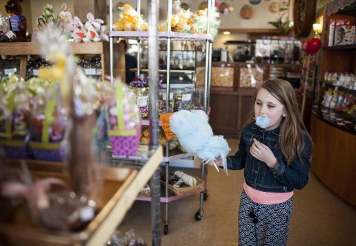 Cali Melidis enjoys a hunk of cotton candy before browsing for Easter candy at Aunt Diana's Old Fashioned Fudge.   William Camargo/Staff Photographer