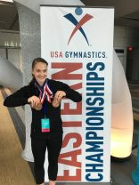 Amanda Gruber proudly shows the four medals she earned at the USA Gymnastics Level 9 Eastern National Championships. (Photo by DeAnn Gruber)