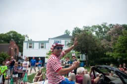Riverside Township Lions Club President Alex Gallegos, wearing his best patriotic finery, waves to the crowd from atop a convertible. | WILLIAM CAMARGO/Staff Photographer