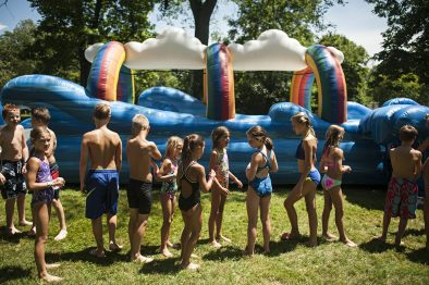 Children line up for the water slide set up outside the Riverside Swim Club. | William Camargo/Staff Photographer