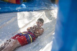 Eddie Melidis slides down a water slide set up outside the Riverside Swim Club. | William Camargo/Staff Photographer