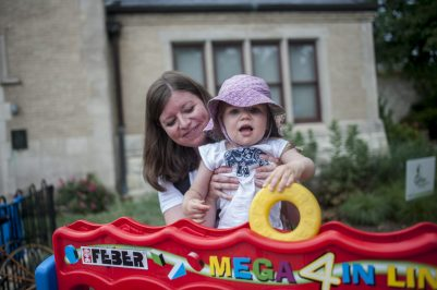 Kathy and 2-year-old Madeline play connect four together during Riverfest. | William Camargo/Staff Photographer