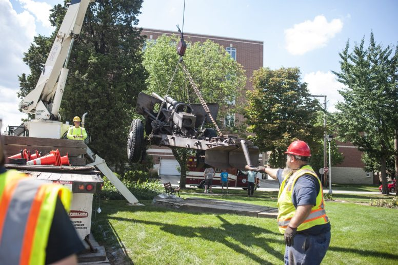A Brookfield Public Works employee steadies the cannon as a crane lifts it off its concrete base before loading the gun onto a trailer and off to be refurbished. A new concrete pad will be poured and the gun replaced in the next few months | William Camargo/Staff