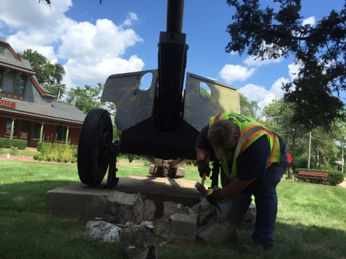 A Brookfield Public Works employee removes the bronze plaque, cast in 1935 when the American Legion dedicated the gun as a war memorial, from the concrete marker in front of the cannon. | Bob Uphues/Staff
