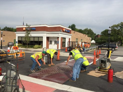 Workers place a metal mat over the roadway to create a stamped asphalt crosswalk last week on East Burlington Street. | BOB UPHUES/Staff