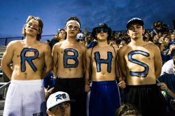 Mike Maggos (R), Sean Kinmp. (B), Matt Towner (H), and Sam Fletcher (S), wear their school pride on their chests in the stands of the Martin Kennelly Athletic Complex at Riverside-Brookfield High School during the Bulldogs' 32-0 rout of Wheaton Academy during the school's homecoming football game on Sept. 23.   Sebastian Hidalgo/Contributor