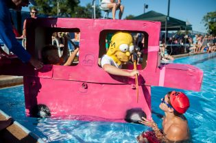 "Alec Wilkowski dressed as Homer Simpson inside his ""station wagon"" boat at the 3rd Annual Cardboard Boat Regatta at the Riverside Swim Club. 